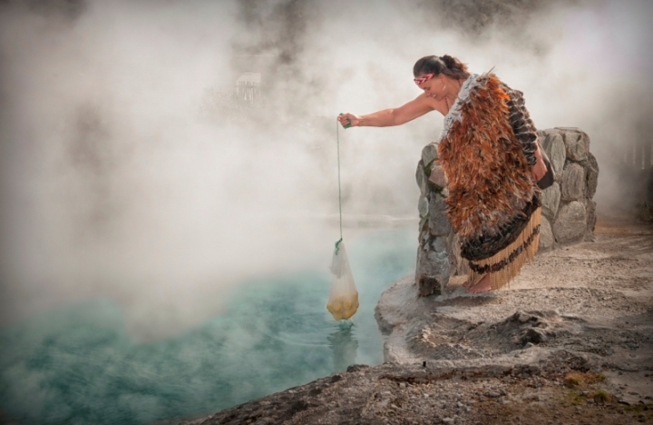 Whakawera-Rotoruas-living-maori-village-girl-cooking-corn-in-hot-pool